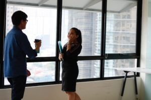 male employee and female employee talking in front of a window