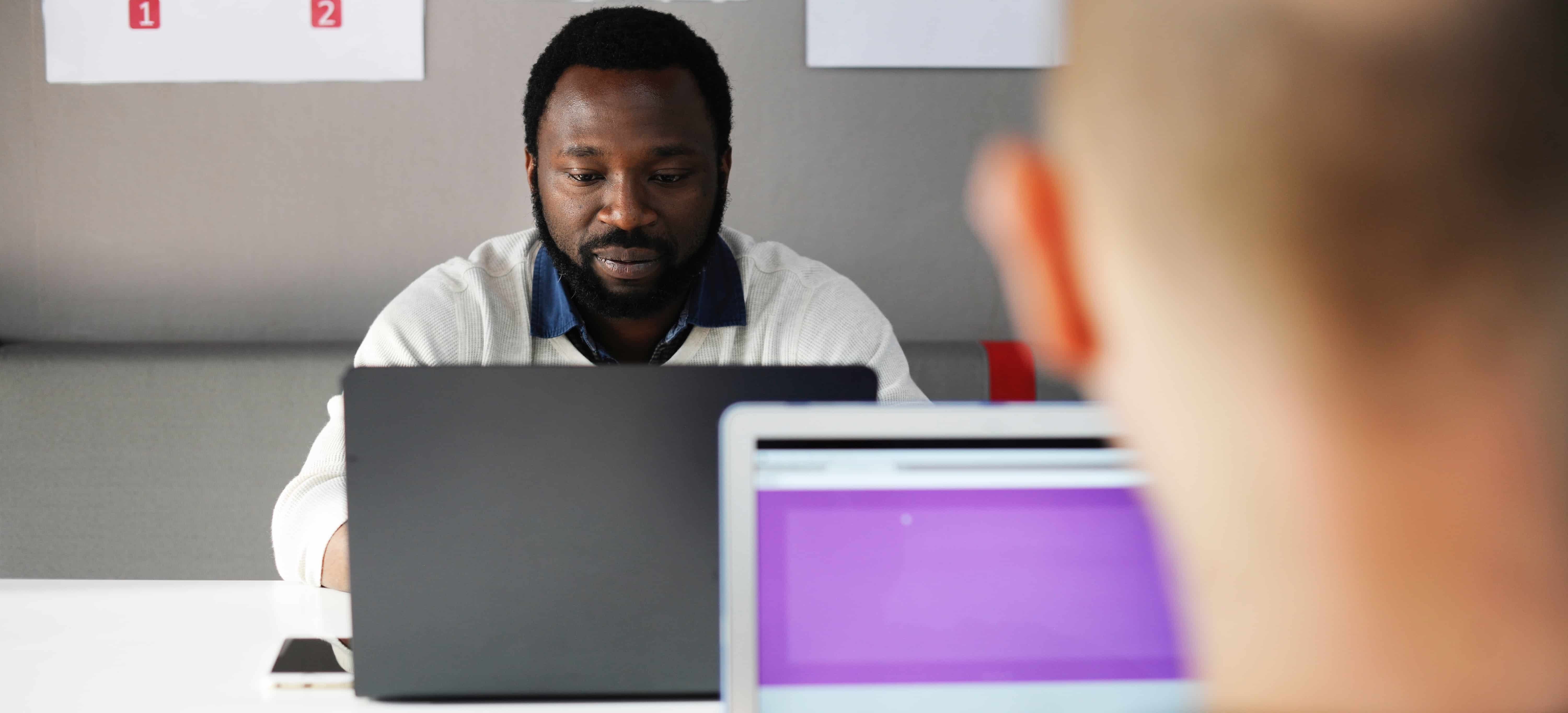 man working at laptop with another man working at laptop out of focus